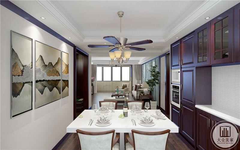 餐厅餐桌餐椅都采用红木材料,一侧的墙面采用三幅拼合的中式风格装饰画,另一的墙面采用马赛克砖墙面装饰。
