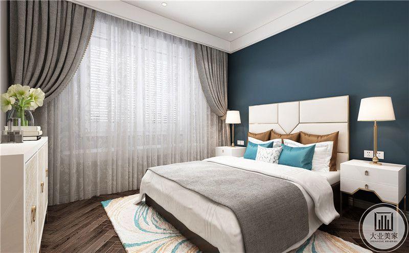 卧室装修效果图:卧室背景墙采用深蓝色,深色木地板搭配白色地毯,白色大床的两侧就是白色床头柜。