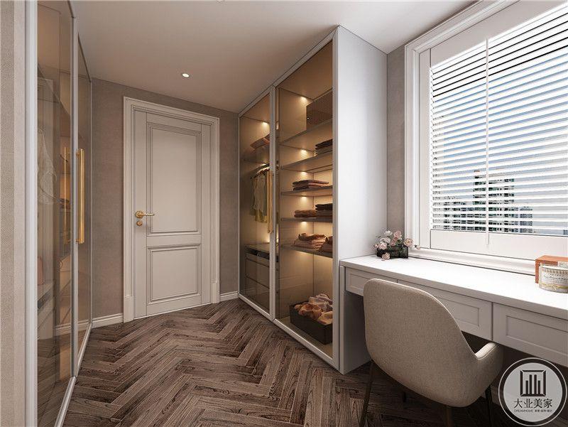 衣帽间装修效果图:衣帽间在放置大量衣柜的同时,在窗户下面添置书桌。