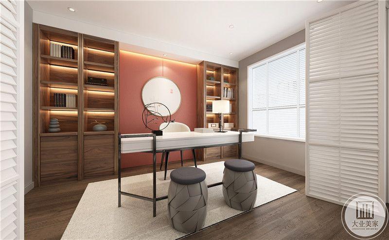 书房采用橘红色背景墙,墙面悬挂中式装饰画,书桌采用黑色金属框搭配白色书桌。