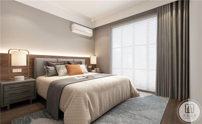 次卧床头背景墙采用灰色壁纸装饰,床的两侧采用灰色床头柜,地面铺设浅色木地板搭配灰色地毯。