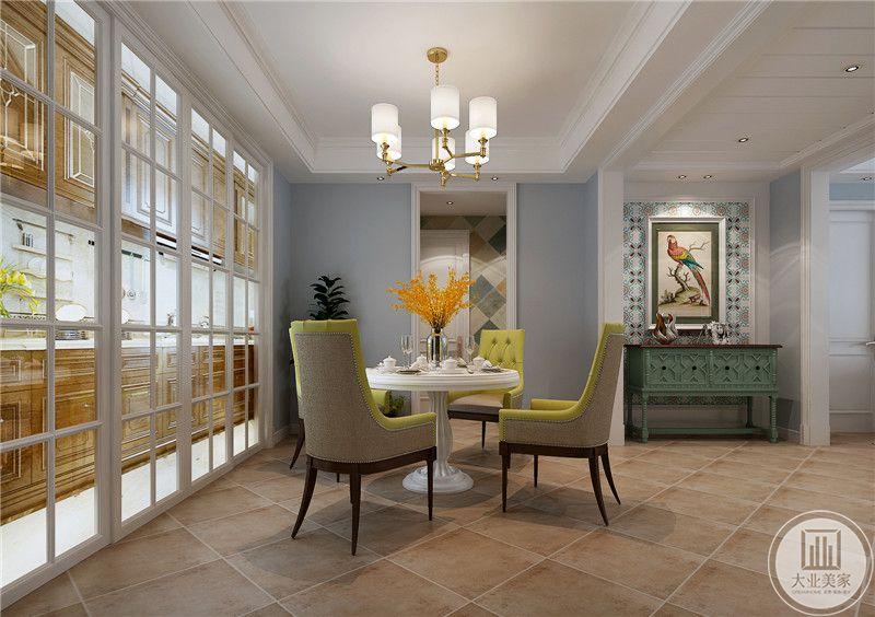 餐厅餐桌采用白色圆桌,搭配抹茶色餐椅,厨房的一侧采用白色实木框架玻璃门。