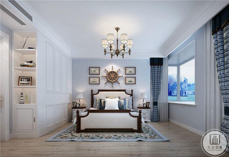 主卧室地面铺设木地板,搭配浅蓝色地毯,床头背景墙采用蓝色装饰,墙面采用现代抽象装饰画搭配船的方向盘。