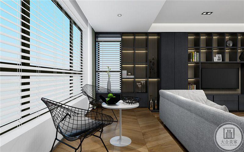 客厅阳台两个黑色座椅搭配白色圆柱茶几,通过沙发区分两个空间。