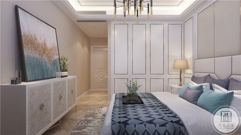 主卧室墙面采用浅黄色壁纸,床尾采用现代装饰画,搭配浅色橱柜。