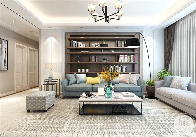 客厅背景墙做成浅色实木书柜,沙发采用浅蓝和米色搭配的效果,地面铺设白色彩砖搭配马赛克式地毯。