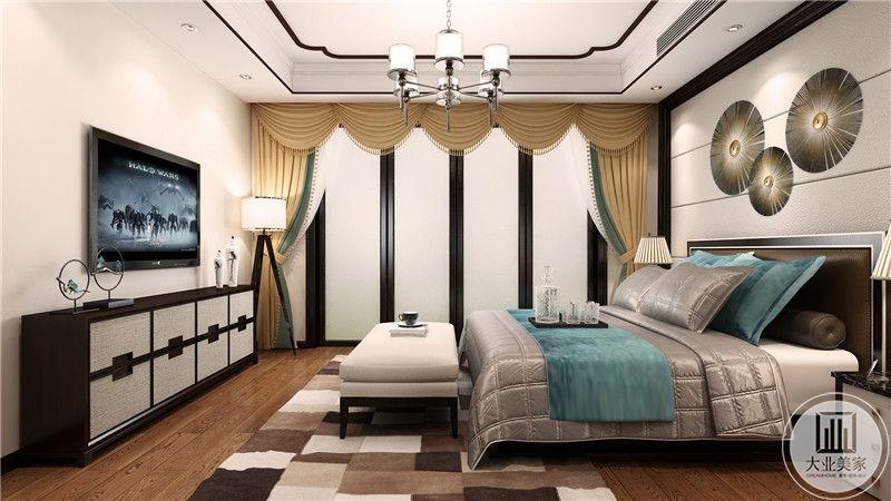 卧室床头背景墙采用白色布艺装饰,墙面采用圆形金属装饰,床尾采用电视机搭配黑灰色电视柜的设计。