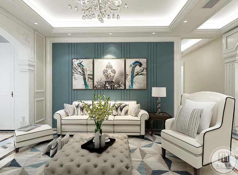 客厅以白色和蓝色为主色调。蓝色漆面的沙发背景墙上是一组灰白蓝为主色调的装饰画。白底黑边的皮质沙发简约大方。