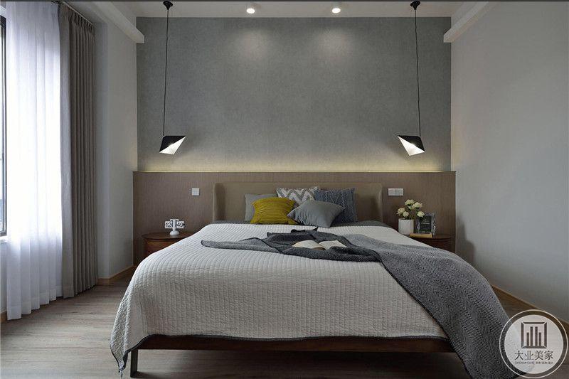 卧室床头背景墙采用灰色护墙板,地板采用浅色木地板。