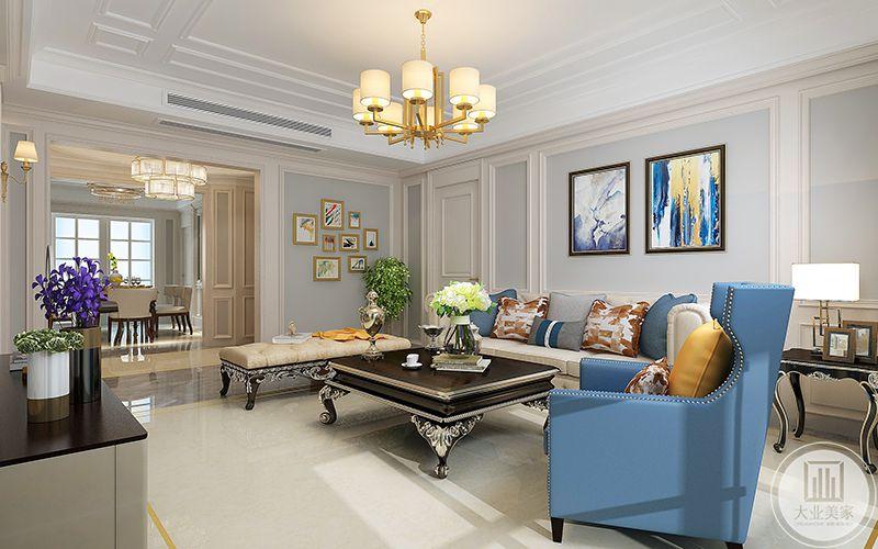 客厅整体是乳白色及钱色调,除却蓝色的单人沙发以及抱枕,在优雅的基础上更添加了明亮的光彩。
