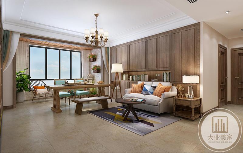 主沙发是一个两人位米色布艺沙发,后面的沙发墙则是用作收纳空间。在客厅与阳台之间设置了一个书案。阳台处也单独放了椅子茶几。