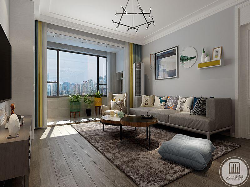 客厅是简约的木质地板,地板上市棕色的地毯,浅灰色的布艺沙发搭配的是圆形的木质台面的组合茶几,沙发背景墙上是装饰画和小小的置物架,阳台明亮,放着大型的盆栽,鹅黄色的窗帘俏丽清新
