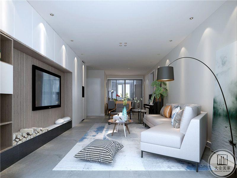 客厅从侧面来看十分干净利落,错落有致。米色的布艺沙发正对电视墙。电视墙设置了护墙板,左侧设置成了收纳空间。