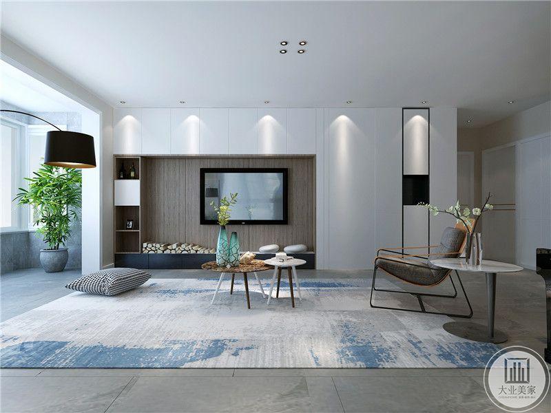 客厅正视图显示整体的设计理念是现代简约。大大的地毯上是小巧精致的组合茶几,电视墙是设计成收纳空间。中间掏空做嵌入式的电视墙。