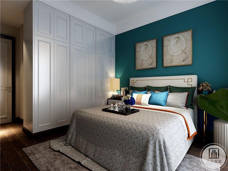 主卧室背景墙是孔雀蓝色调,大气沉稳,孔雀蓝色的背景墙上是两幅简单的艺术画,使卧室文化气息浓厚
