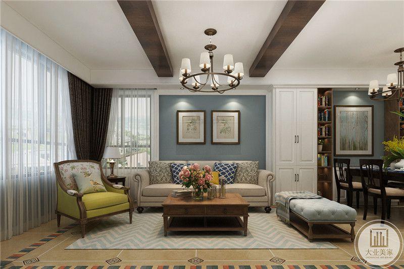 沙发墙则是蓝色为底,上面装饰了两幅插画,沙发是米白的布艺沙发和一个浅蓝色的榻