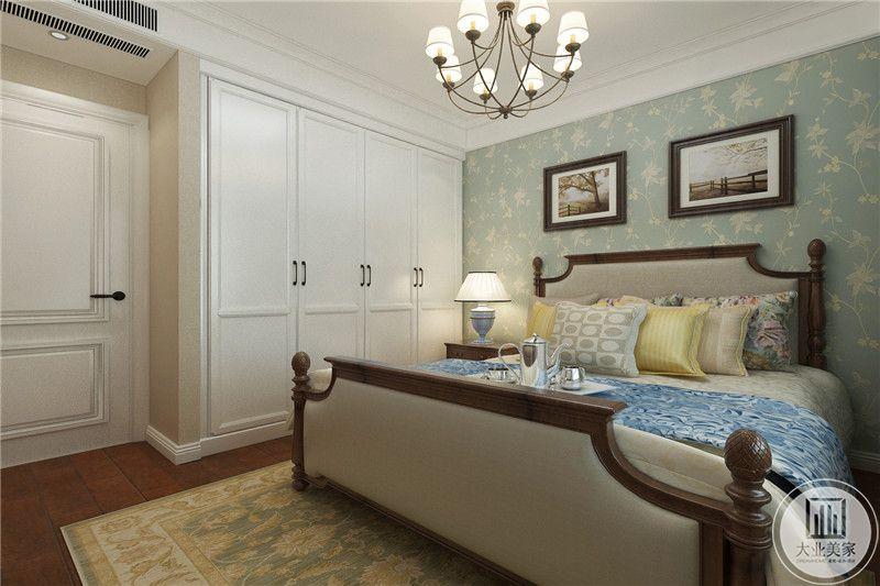 主卧室是复古的家居床,床头墙是清新的蓝底白纹壁纸,与复古的床品完美契合