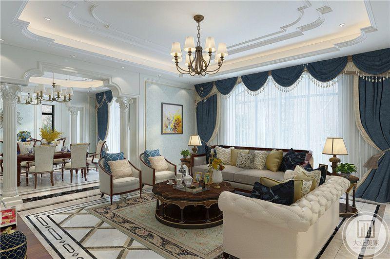 客厅是乳白色的布艺沙发,整体是白色和灰蓝色两种色调,美式的吊灯下是小巧的圆形木质茶几,地毯也是与整体风格相符合的美式纹样
