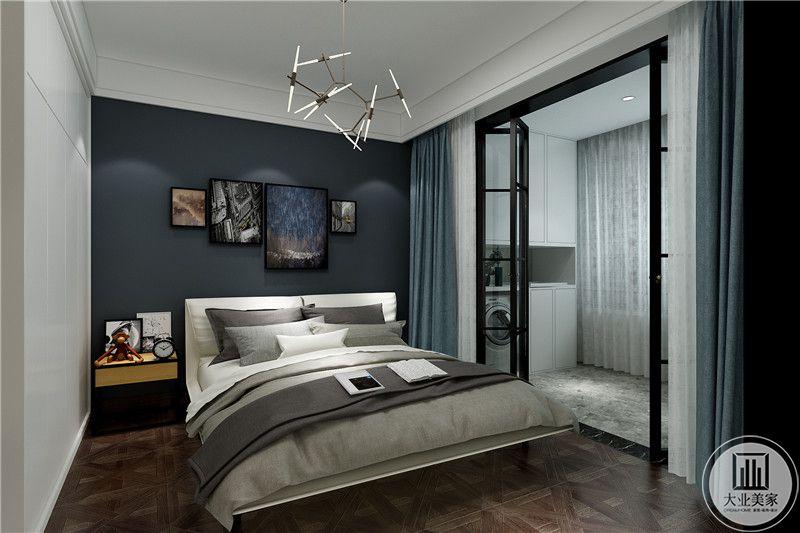 次卧带着一个阳台,阳台上有滚筒洗衣机,卧室与阳台用黑框架的玻璃门隔开。