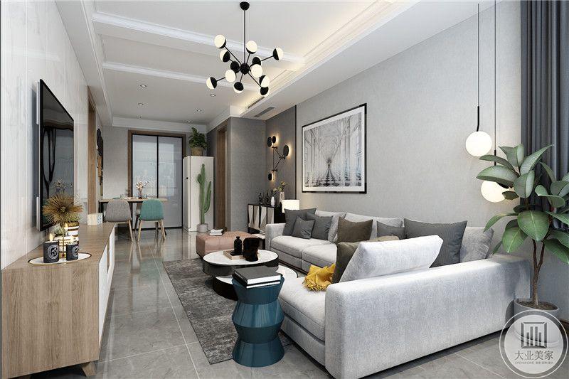 客厅是简约的白色布艺沙发和浅灰色的抱枕,沙发墙左侧是艺术挂画
