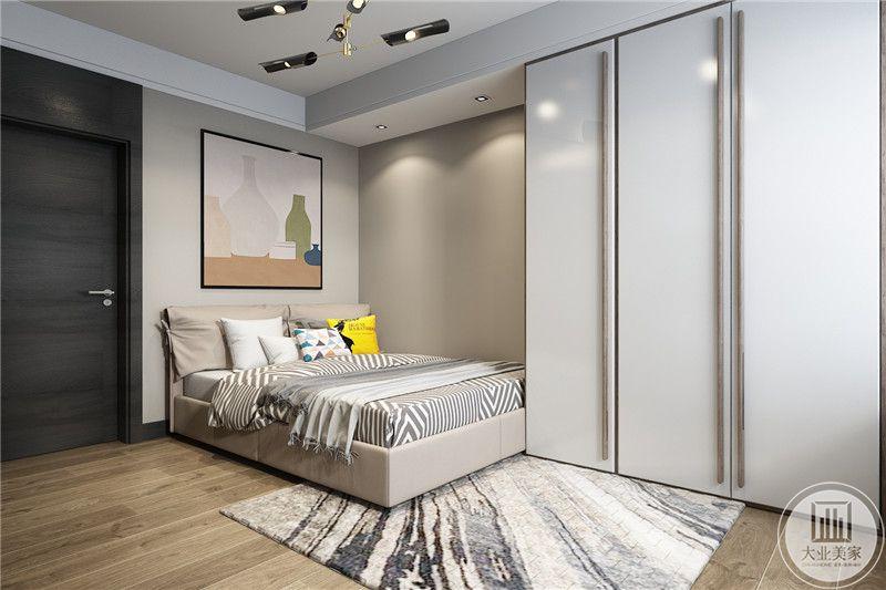 次卧设置在门侧,空间较小,较宽的双人床头装饰着暖色调的装饰画