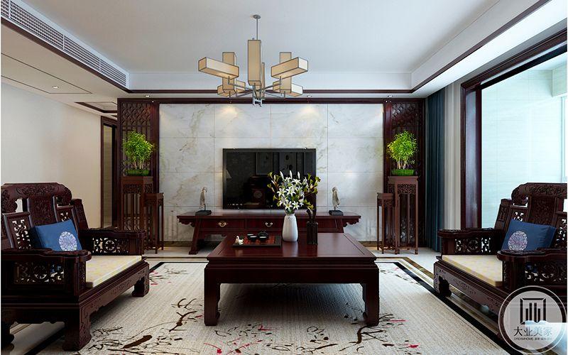 电视墙是乳白色大理石板,与整套的红木家具形成鲜明对照