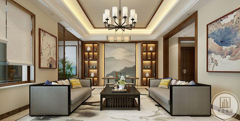 客厅是极其对称的,两侧的浅灰色的布艺沙发中间是黑色的方形茶几,茶几上摆着茶具和插花,优雅方正,茶几对面是中式的书房空间,背景墙是水墨的山水图,图两侧是储物架,放着摆件和装饰品