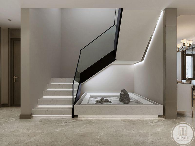 楼梯设计的简约而不简单,白色的大理石板材和玻璃扶手,楼梯角是水和山石的设计,尽显极简主义的意境