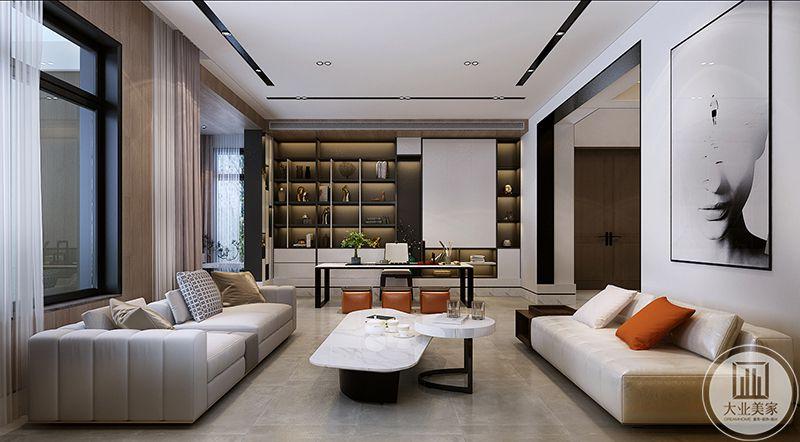 客厅与书房设置在一个空间。浅色的大理石地板上是两组皮质沙发和白色的组合茶几,沙发一旁的装饰墙上海装饰着一幅超大的艺术画