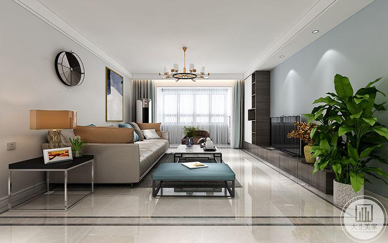客厅地面是大理石板材,沙发是浅棕色的皮质沙发,电视柜与储物架设置成一个L形,电视墙面则是灰蓝色的墙面。电视一旁还放着一个大型盆栽,绿油油的盆栽使客厅添了一些生机