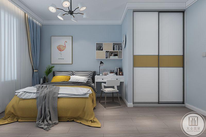 儿童房布置简约清新,浅蓝色的墙面,安黄色的被褥搭配和谐,床头旁还配了简单的书桌椅