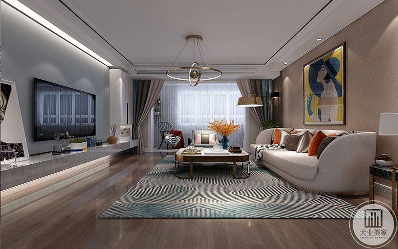 客厅地面是浅木色的地板,地板上是条纹地毯,米色的沙发上是暖色系的抱枕,沙发墙是浅棕色调,中央是一幅艺术装饰画,金白色的茶几极富轻奢感