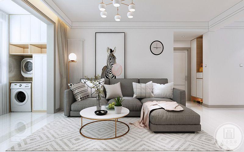 客厅是浅灰色的布艺沙发,回字纹的地毯上是圆形的简约茶几,茶几上是果盘和插花,在这个角度能够看得见阳台的滚筒洗衣机和收纳柜