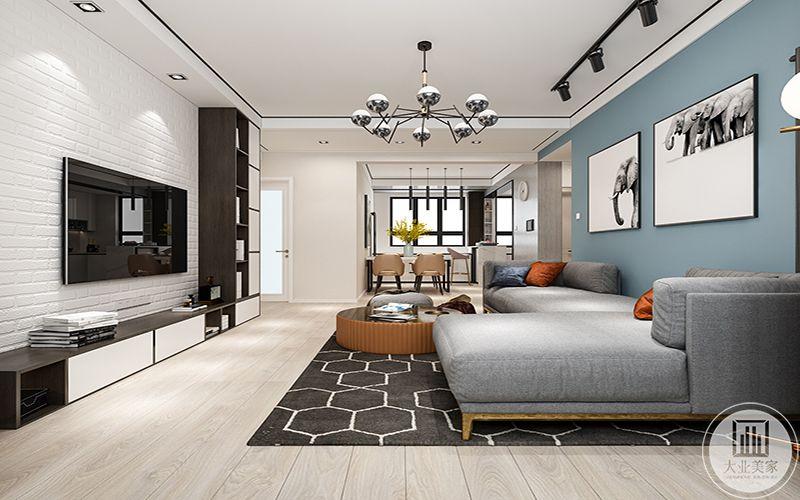 客厅地面是浅木色的地板,浅灰色的布艺沙发后面是浅蓝色的沙发墙,沙发墙上是两幅黑白的艺术画
