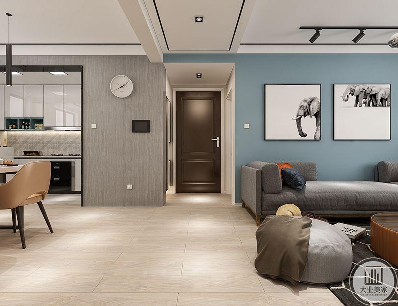 在这个角度可以看得见厨房的是简约大方的白色的橱柜,厨房外侧的墙面是浅灰色得漆面,上面挂着一只圆形的时钟