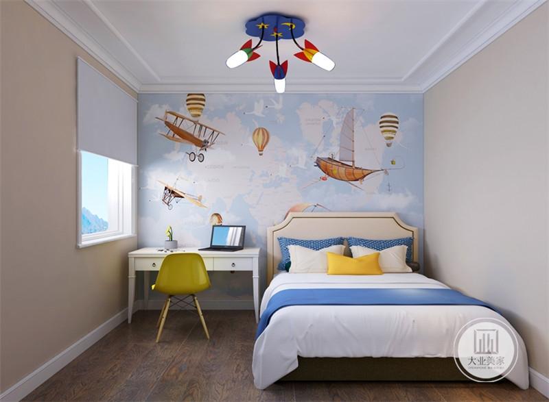 儿童卧室床头背景墙铺贴蓝色卡通风的壁纸,靠窗的一侧采用白色书桌。