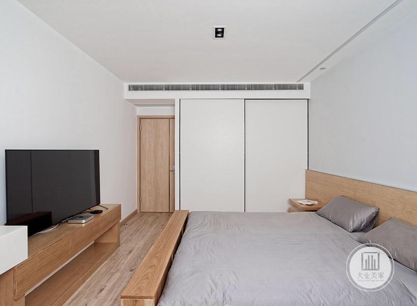 床尾放置原木电视柜,白色衣柜柜门采用推拉门的设计。
