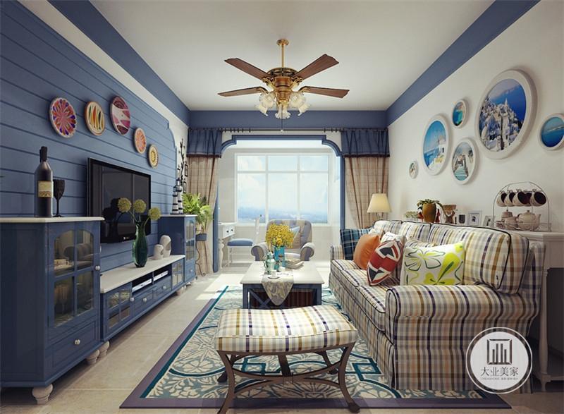 客厅影视墙采用蓝色木板装饰,下方电视柜和两侧橱柜都采用蓝色装饰,客厅阳台放置白色书桌和翼子。